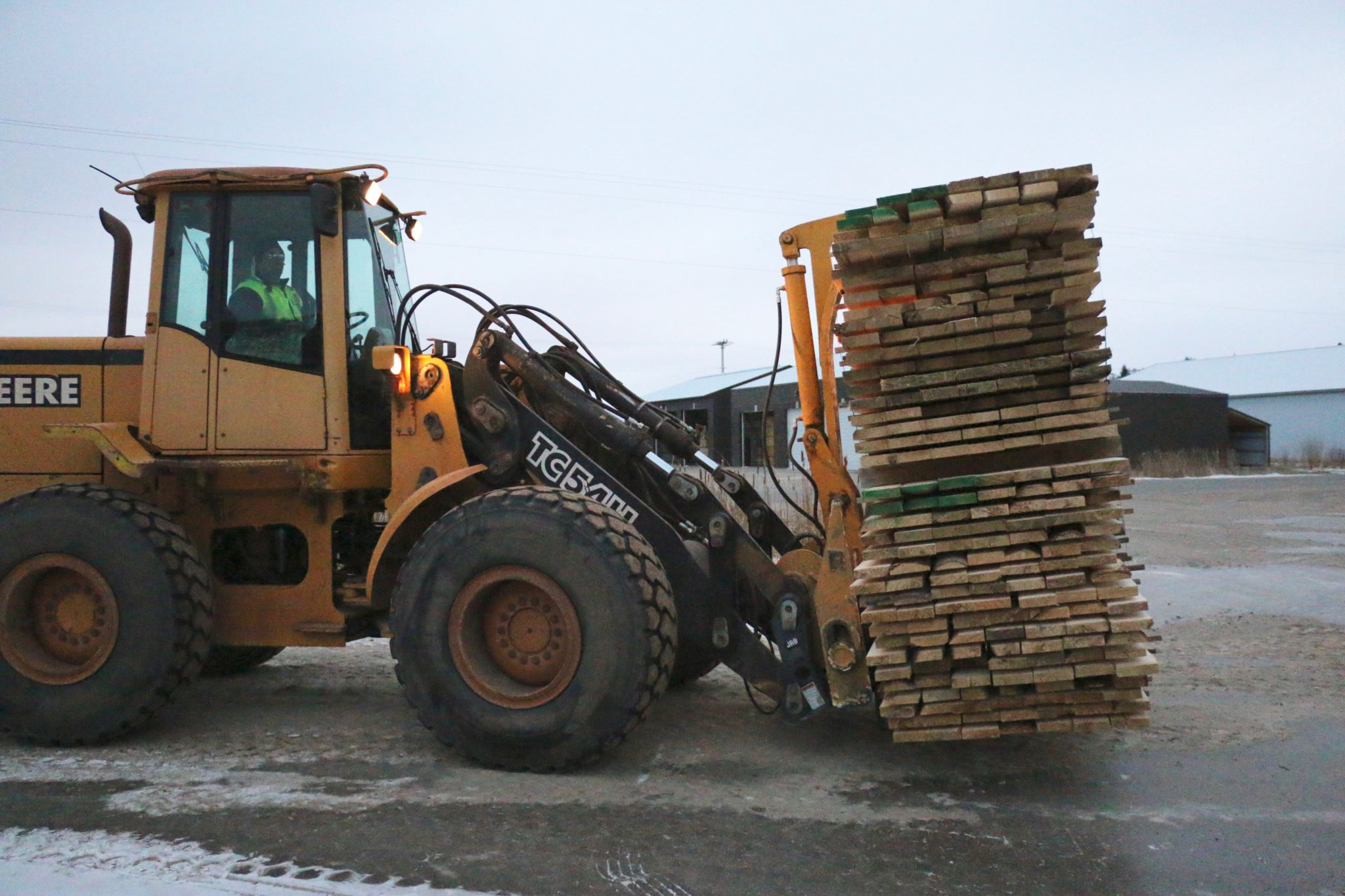 A Nelson Wood Shims employee operating a forklift, transporting boards to be made into shims